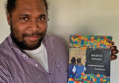 Man holding a copy of new WASH in Schools guide
