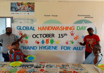 Live & Learn staff stand in front of banner that says Global Handwashing Day